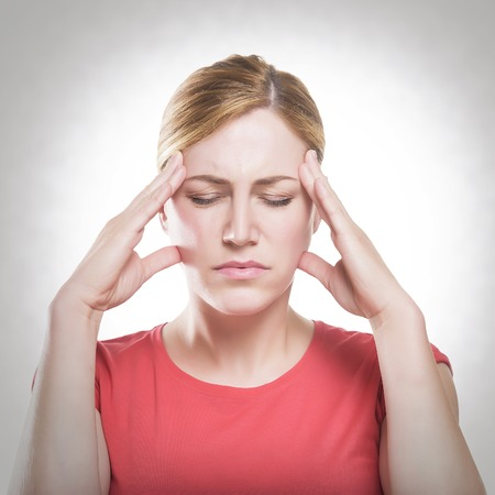 Woman puts hands on the head, toned photo.. Concept of problems and headache.