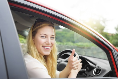 adoring: Happy woman showing thumb up and driving a new car.
