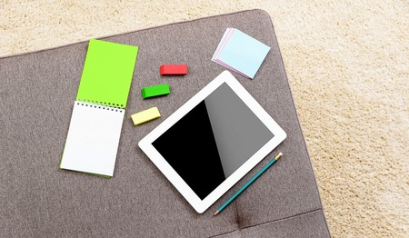 carpeting: Tablet computer and notebook at home on the sofa. Stock Photo