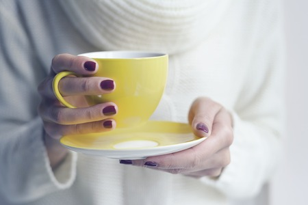 Cup of tea or coffee in female hands close up. Toned photo.