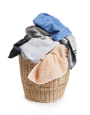Colorful clothes before washing in a straw basket.
