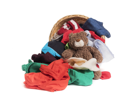 basket: Colorful clothes and toy Teddy bear before washing in a straw basket.