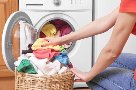 Preparing the wash cycle. Washing machine, hands and clothes.