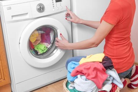 Frau Laden der Waschmaschine farbige Kleidung.