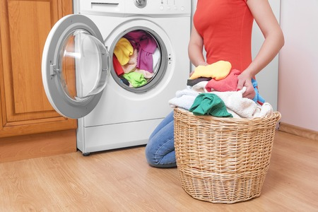 Woman loading the washing machine colored clothing. Archivio Fotografico