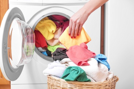 washing clothes: Woman loading the washing machine colored clothing. Stock Photo
