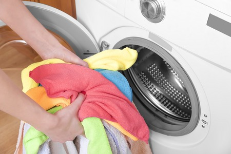 Woman loading the washing machine colored clothing. Stock fotó