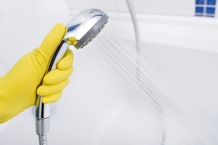 cleaning bathroom: Shower in the hands of cleaning the bathroom. Stock Photo