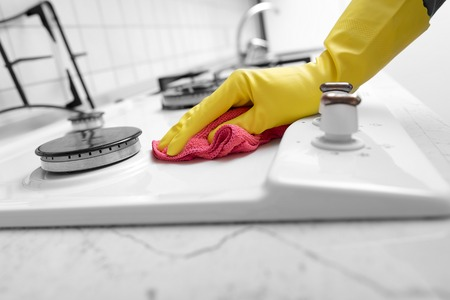 Hands in yellow gloves washing the gas stove.