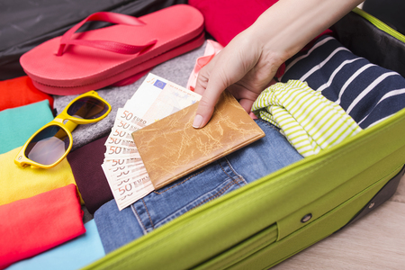 warm things: Open suitcase with things for relaxation close-up. Hand puts a passport and money in a suitcase. Stock Photo