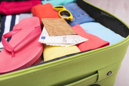open suitcase: Open suitcase with things for relaxation close-up.