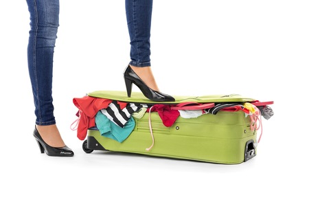 overfilled: Female feet in shoes on a suitcase. White background.