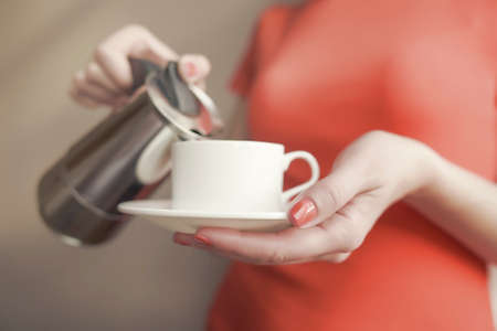 pours: Female hand pours coffee from a the coffee maker. Focus on the hand. Stock Photo