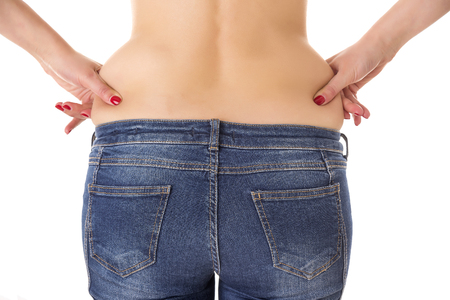 carb: Woman hands compresses the the fat on the waist on a white background.