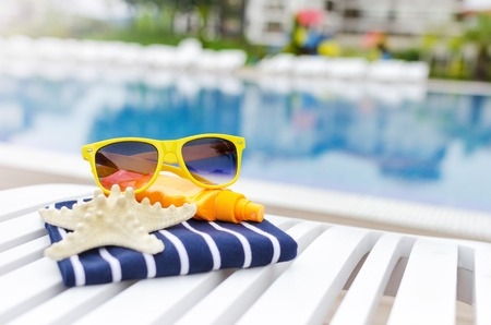beach summer: Sunglasses and the things on a poolside lounger. Stock Photo