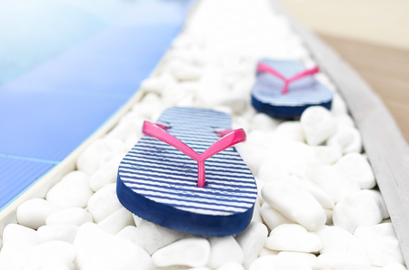 bluer: Flip flops at the pool on the white pebbles. Close-up.