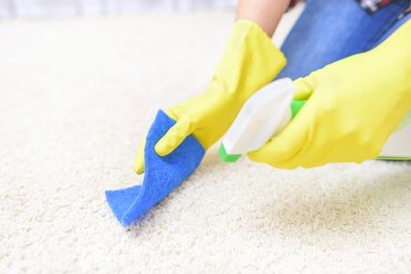 Aerosol de limpieza de alfombras. De cerca. Centrarse en un trozo de tela y alfombras. Foto de archivo