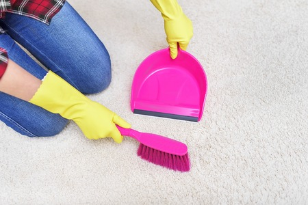 keeping room: Female hands in yellow gloves sweeping a carpet brush.