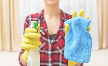 Woman wash that something spray and cloth. Focus on the spray. Stock fotó