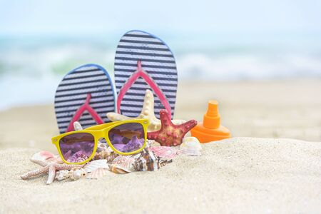 swimming shoes: Flip-flops and shells on the beach. Summer Still Life. Stock Photo
