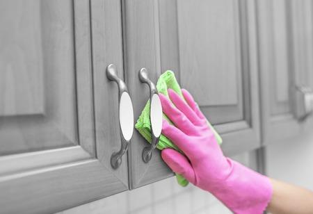 De handschoenen van vrouwen wrijven het stof uit de deur van de kast. Detailopname.