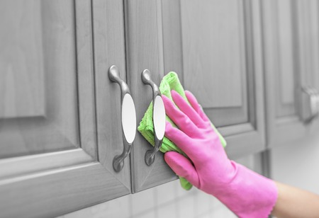 mano enguantada de las mujeres limpie el polvo de la puerta del armario. De cerca.