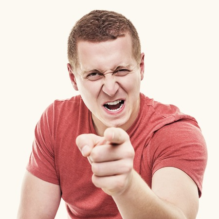 reproach: Young man on white background menacingly points a finger. Toned photo.