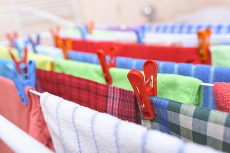 Beautiful multi-colored clothes drying in the dryer. Stock Photo