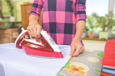 white washed: The woman to iron the clothes on an ironing board. Stock Photo