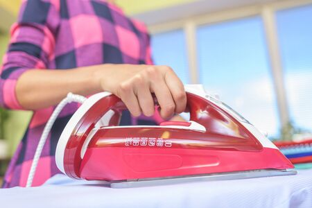 The woman to iron the clothes on an ironing board. Stock Photo