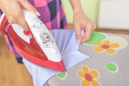 Ironing a shirt collar on the ironing board.