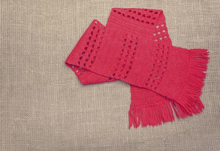 red scarf: A red scarf on the background of burlap.
