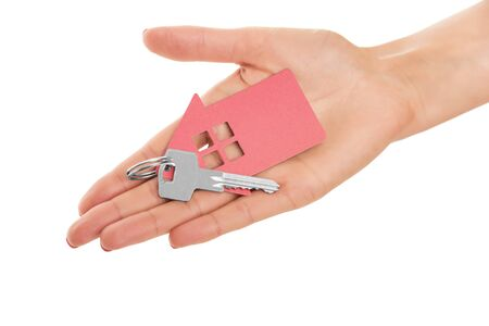 Hand holds key with a keychain in the shape of a house on a white background. Stock Photo