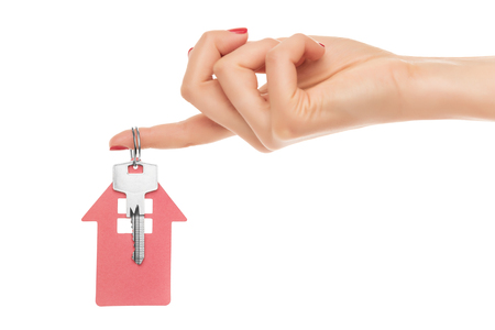 downpayment: Hand holds key with a keychain in the shape of a house on a white background. Stock Photo