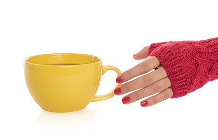 ingram: Female hand in a mitten reaches for a cup of tea on a white background.