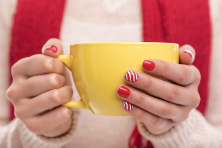 Womens hands holding a cup of drink. Winter clothes.