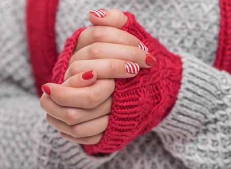 A woman warms the frozen hands in mittens.
