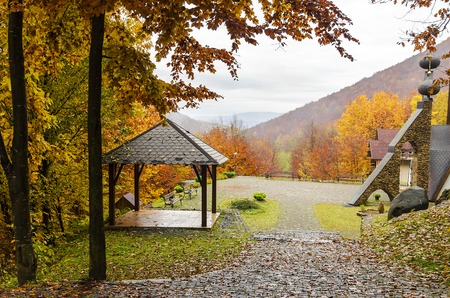 A wooden a gazebo in the mountains in autumn.