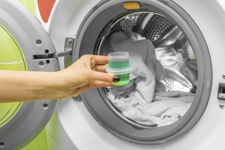 Hand pours liquid powder into the washing machine. Stock fotó