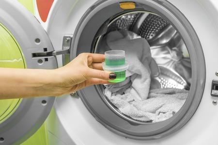 Hand pours liquid powder into the washing machine. Фото со стока