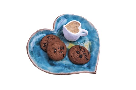Saucer and cup with coffee in the shape of heart and cookies.