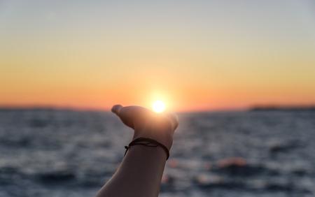 手は日没時に太陽に手を伸べる。 写真素材