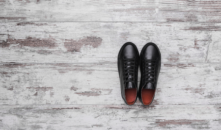 Black leather sneakers on a light laminate. Banco de Imagens