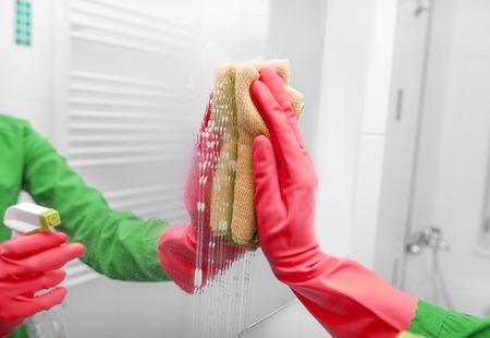 Hands in gloves wash the mirror. Zdjęcie Seryjne