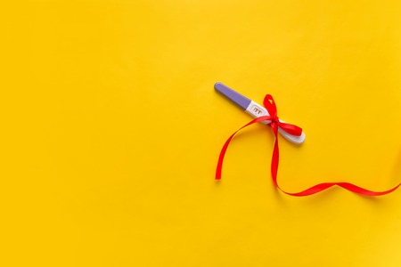 Pregnancy test on a yellow background. The result is positive. Two strips.