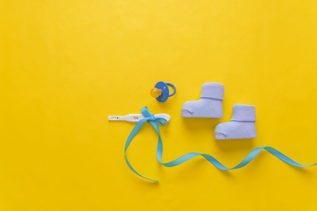 Baby socks and a pregnancy test on a yellow background.