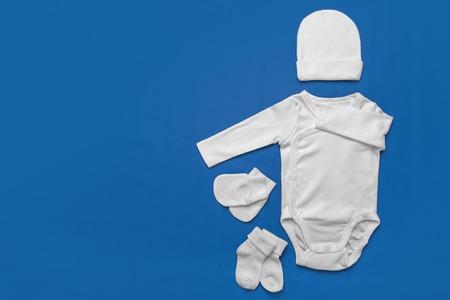 Satz weiße Babykleidung auf blauem Hintergrund. Standard-Bild