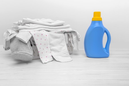Bottle with liquid detergent against the background of the basket with baby clothes.