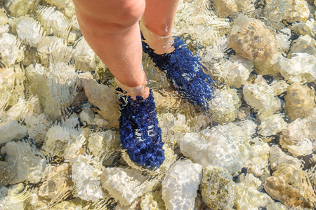 Feet in the water wrapped in special shoes to protect from sea urchins.