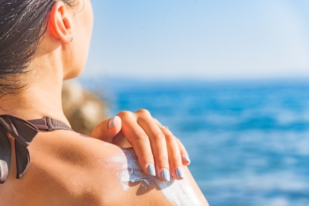 Beautiful young woman is smearing her body with sunscreen on the background of sea. Banco de Imagens
